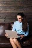 Glücklicher Brunette, der auf Sofa im Wohnzimmer unter Verwendung des Laptops sitzt Stockfotos