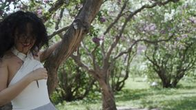 Glücklicher Brunette, der für Kamera im Sommergarten aufwirft stock video