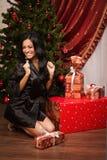 Glücklicher Brunette, der nahe einem Weihnachtsbaum mit Geschenken sitzt Lizenzfreie Stockfotos