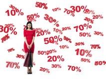 Glücklicher Brunette in einem roten Kleid mit den Einkaufstaschen Rabatt- und Verkaufssymbole: 10% 20% 30% 50% 70% Lizenzfreies Stockfoto