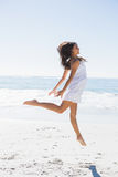 Glücklicher Brunette im weißen Sonnenkleidertanzen auf dem Sand Stockfotos