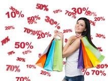 Glücklicher Brunette mit den bunten Taschen Rabatt- und Verkaufssymbole: 10% 20% 30% 50% 70% Lizenzfreie Stockfotos