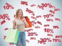 Glücklicher Brunette mit den bunten Taschen Rabatt- und Verkaufssymbole: 10% 20% 30% 50% 70% Stockfotografie