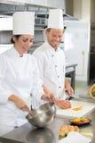 Glücklicher Chef mit schönem lächelndem weiblichem Assistenten an der Küche stockbild