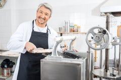 Glücklicher Chef Processing Ravioli Pasta in der Maschine Lizenzfreie Stockbilder