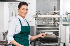 Glücklicher Chef Processing Ravioli Pasta in der Maschine Stockfotografie