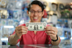 Glücklicher chinesischer Mann, der erstes Dollar-Einkommen im Computer-Shop zeigt Stockfotos