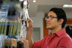 Glücklicher chinesischer Mann, der Usb-Antrieb im Computer-Shop bestellt Stockfoto