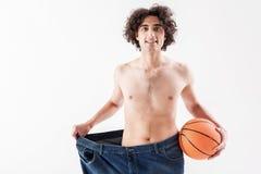 Glücklicher dünner Sportler, der seinen Gewichtsverlust zeigt Lizenzfreie Stockfotos
