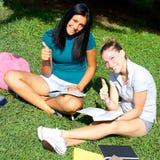 Glücklicher Daumen mit zwei Studentinnen oben lizenzfreie stockfotografie