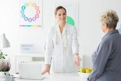 Glücklicher Diätetiker mit Maßband stockbild