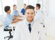 Glücklicher Doktor über Gruppe Medizinern am Krankenhaus Lizenzfreies Stockbild