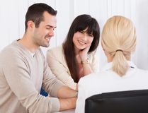 Glücklicher Doktor Discussing With Couple Lizenzfreies Stockfoto
