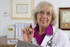 Glücklicher Doktor in ihrem Büro Lizenzfreie Stockfotos