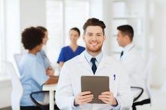 Glücklicher Doktor mit Tabletten-PC über Team an der Klinik Lizenzfreie Stockfotos