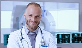 Glücklicher Doktor in MRI-Raum am Krankenhaus lizenzfreies stockbild