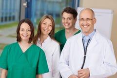 Glücklicher Doktor Team Standing Together In Clinic Stockfotos
