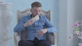 Gl?cklicher durchdachter reicher b?rtiger Mann im blauen Hemd, das im wei?en Lehnsessel im hellen Raum z?hlt Geld sitzt jung stock video