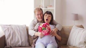 Glücklicher Ehemann, der seiner schwangeren Frau Blumen gibt stock footage