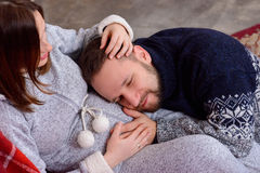 Glücklicher Ehemann hört auf den Babyherzschlag, der auf Bauch seiner schwangeren Frau liegt Stockbild