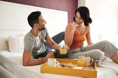 Glücklicher Ehemann und Frau, die Frühstück im Bett isst stockfotografie