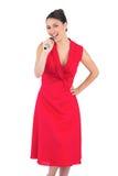 Glücklicher eleganter Brunette im roten Kleid singend Lizenzfreie Stockfotos
