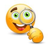 Glücklicher Emoticon, der durch Vergrößerungsglas schaut Stockfotografie