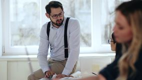 Glücklicher entspannter junger europäischer Mann-CEO-Geschäftsmann, der mit dem Kollegen sitzt auf Tabelle am modernen Büroarbeit stock video