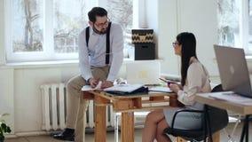Glücklicher entspannter junger männlicher Chefgeschäftsmann, der mit dem weiblichen Kollegen sitzt auf Tabelle am modernen Dachbo stock footage