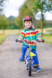 Glücklicher entzückender Kinderjunge im Schutzhelm auf Fahrrad Lizenzfreies Stockfoto