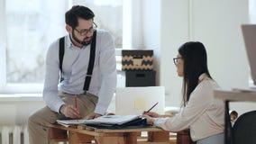 Glücklicher ernster junger CEO-Geschäftsmann, der mit dem schönen weiblichen Kollegen sitzt auf Tabelle im modernen bequemen Büro stock video footage