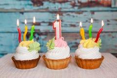 Glücklicher erster Geburtstagskuchen und Nummer Eins-Kerze auf blauem Hintergrund lizenzfreies stockfoto