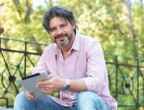 Glücklicher erwachsener gutaussehender Mann, der draußen sitzen und Tablette Lizenzfreie Stockbilder
