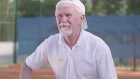 Glücklicher erwachsener Mann, der Tennis an einem sonnigen Tag spielt Erholung und Freizeit draußen stock video footage