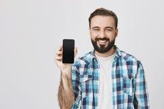 Glücklicher europäischer Mann mit Bart und Schnurrbart, der smarphone zur Kamera beim während der Werbung breit lächeln zeigt Lizenzfreie Stockfotos