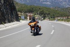 Glücklicher Fahrer, der Harley Davidson auf die Straße reitet stockfotos