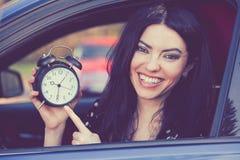 Glücklicher Fahrer der jungen Frau innerhalb ihres Autos, das Wecker zeigt lizenzfreies stockbild