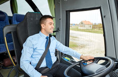 Glücklicher Fahrer, der mit Mikrofon spricht und Bus fährt Stockfotografie