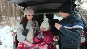 Glücklicher Familiengetränktee und die Winterlandschaft genießen Familienurlaub im Winterwald stock video