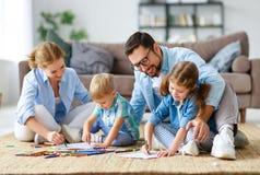 Glücklicher Familienmuttervater und -kinder zeichnen zusammen zu Hause stockfotografie