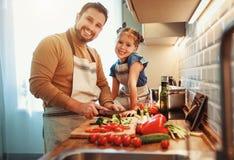 Glücklicher Familienvater mit der Kindertochter, die Gemüsesalat zubereitet lizenzfreies stockbild