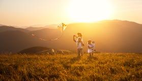 Glücklicher Familienvater, -mutter und -kinder starten Drachen auf Natur stockbild