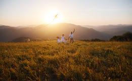 Glücklicher Familienvater, -mutter und -kinder starten Drachen auf Natur bei Sonnenuntergang stockbilder