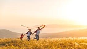 Glücklicher Familienvater, Mutter und Kindertochter starten einen Drachen an Lizenzfreies Stockfoto