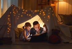 Glücklicher Familienvater und -kinder, die ein Buch im Zelt am hom lesen Stockfoto