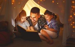 Glücklicher Familienvater und -kinder, die ein Buch im Zelt am hom lesen