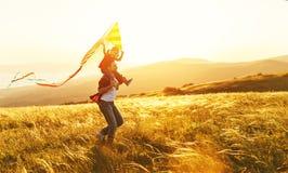 Glücklicher Familienvater und Kindertochter laufen mit Drachen auf Wiese Lizenzfreies Stockbild