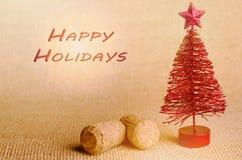 Glücklicher Feiertag geschrieben in Rot Roter künstlicher Weihnachtsbaum mit Champagnerkorken auf hellem Hintergrund Stockbild