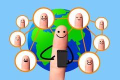 Glücklicher Finger unter Verwendung des Handys mit Weltkarte, Konzept des Sozialen Netzes. Stockfotografie