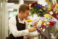 Glücklicher Florist im Schutzblech nahe bei vielen Blumensträußen auf einem Blumenladenhintergrund Kleinbetriebkonzept lizenzfreies stockbild